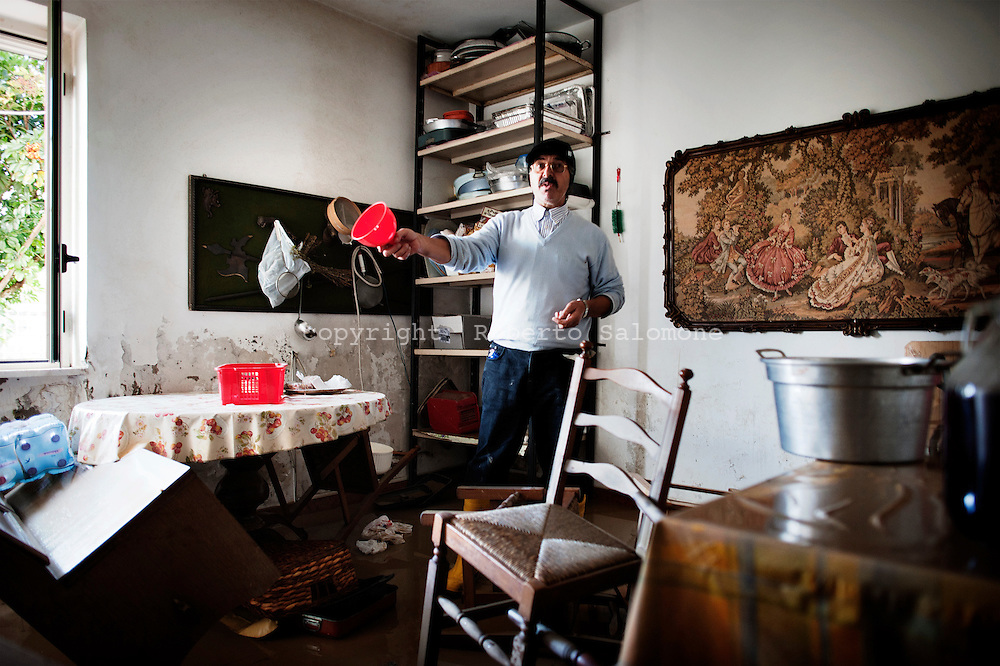 ITALY, Gromola : A man shows the damages suffered by his house after a flooding hit his house on November 11, 2010. The flloding caused severe damages to the agricolture and buildings in the towns of gromola, Capaccio and Capaccio Scalo. AFP PHOTO / ROBERTO SALOMONE