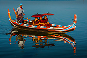 monks under parasols in canoe on Inle lake, Myanmar, Shan state