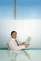 Business man holding document at table in conference room portrait