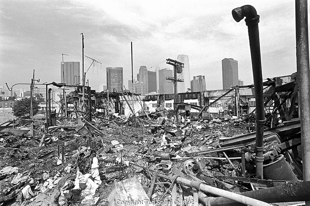 The skyline of downtown Los Angeles is seen in the background of a burned down apartment building on Olympic Blvd. in the Pico/Union area of Los Angeles.