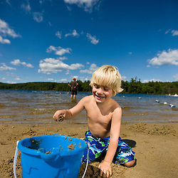 A boy plays on the beach at Otter Lake in Greenfield State Park in Greenfield, New Hampshire.