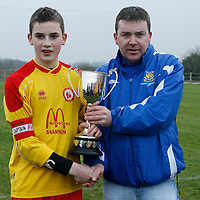 Avenue's Captain Donal O'Halloran receives the Dr Bhamjee U13 Cup from Ronnie Pyne Clare Schoolboy's Soccer League.<br />Photograph by Flann Howard
