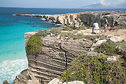 A couple of holidaymakers with bicycles survey the view and turquoise waters of Cala Rossa on Favignana Island, Aegadian Islands (Isole Egadi), western Sicily, Italy.