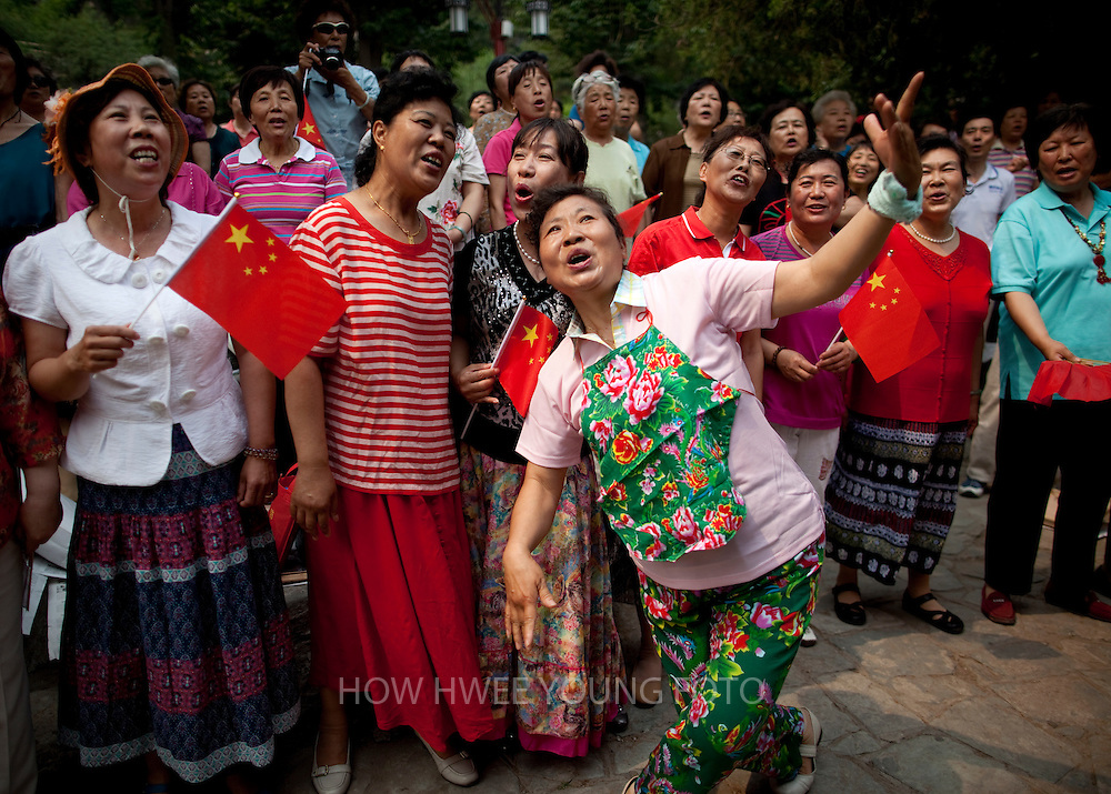 epa02779238 Chinese residents sing 'red songs' or songs that praise the ruling Communist Party during a performance organized by the Beijing Municipal Government office in Jingshan Park of Beijing, China on 14 June 2011. China's 'red' push gains momentum with the approach of the 90th anniversary of the Chinese Communist Party on 01 July and it is not uncommon to see groups of retirees and elderly citizens gathered in parks and open spaces, mostly on weekends, singing and dancing to songs that pay homage to the ruling party.  EPA/HOW HWEE YOUNG
