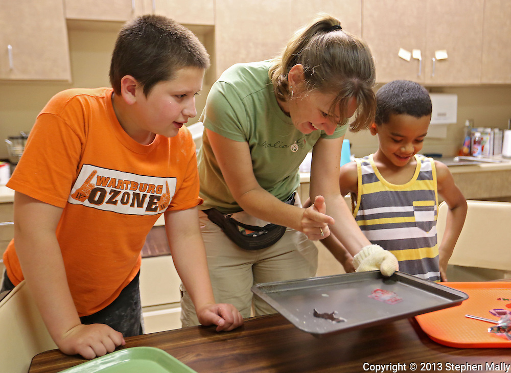 Teacher Shandra Sarasio Meyer (center) signs as she talks with Noah Fink (left), 10 of Waverly and Peyton Tshilumba (right), 8, of Kalona as they look at their shrinky dinks craft right out of the oven during a summer camp hosted by the Iowa School for the Deaf at the Iowa Braille and Sight Saving School in Vinton on Tuesday, July 16, 2013. Sarasio Meyer is a teacher with Area Educational Agency 267 in Forest City.