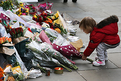 A young child lays flowers outside South Africa House in London, Friday, 6th December 2013, following the death Nelson Mandela, Picture by Stephen Lock / i-Images