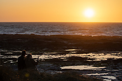 © Licensed to London News Pictures. 02/04/2020. Padstow, UK. A couple watch as the sun sets over Constantine Bay on the north coast of Cornwall after a warm clear day. Warm weather is expected next week. Photo credit : Tom Nicholson/LNP