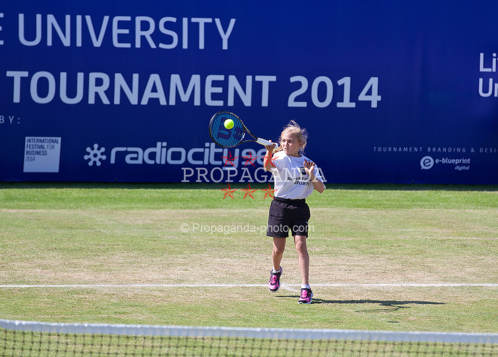 LIVERPOOL, ENGLAND - Saturday, June 21, 2014: A ball girl plays on centre court during Day Three of the Liverpool Hope University International Tennis Tournament at Liverpool Cricket Club. (Pic by David Rawcliffe/Propaganda)