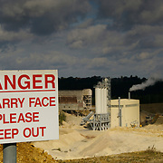 A Danger sign posted above the face of a working quarry with the quarry buildings in the background