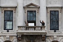 © Licensed to London News Pictures. 30/12/2015. London, UK. Two protesters wave from a balcony of the Royal Mint building. Squatters have occupied the former Royal Mint building, located opposite the Tower of London on the border of the City of London to protest against homelessness and highlight how empty buildings could provide shelter for rough sleepers. The site was previously used to manufacture British coins but is currently vacant and activists argue that this along with other vacant commercial buildings could be used to provide short term shelter for the homeless. Photo credit : Vickie Flores/LNP