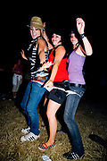 Three girls dancing, wearing one pair of knickers. Global Gathering festival, Long Marston Airfield, Stoke on Trent, UK. 28/29 July 2006