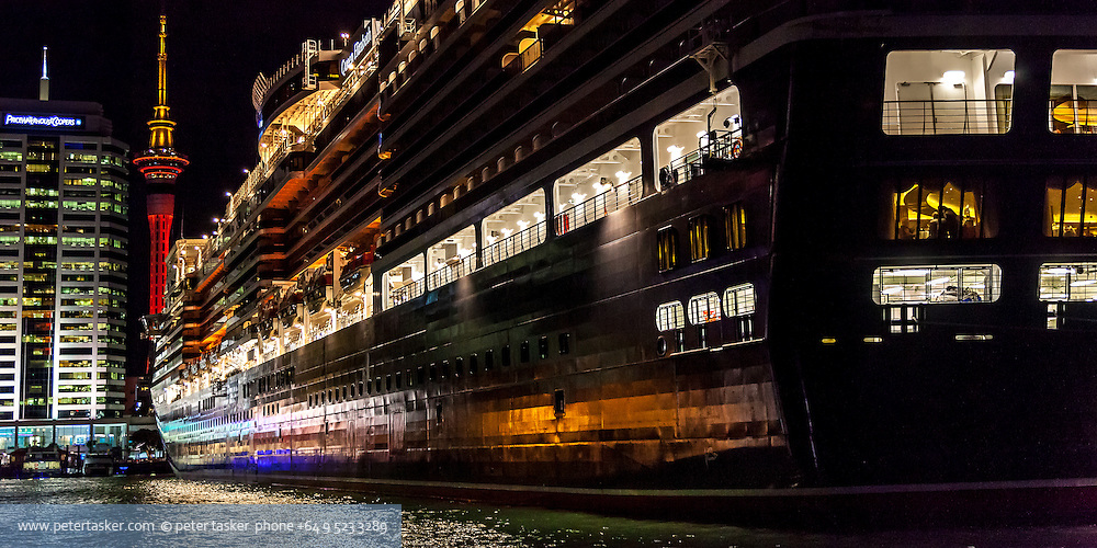 Cruise liner, Queen Elizabeth, along side the Hilton Hotel, Auckland, New Zealand. Photographed at night, with illuminated Skytower in background.