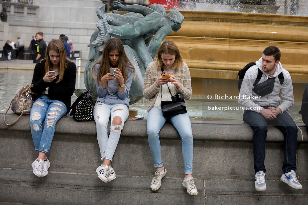 Three teenage girls obsessed with social media, apps and messaging, in Trafalgar Square, London.