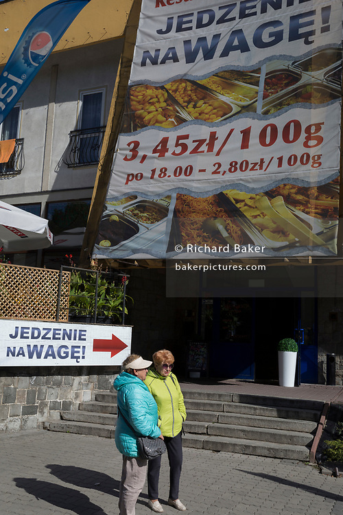 Middle-aged Polish shoppers walk past advertising signs, on 21st September 2019, in Szczawnica, Malopolska, Poland.
