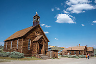 Old Methodist church exterior at Bodie with visitors walking down street of the ghost town.