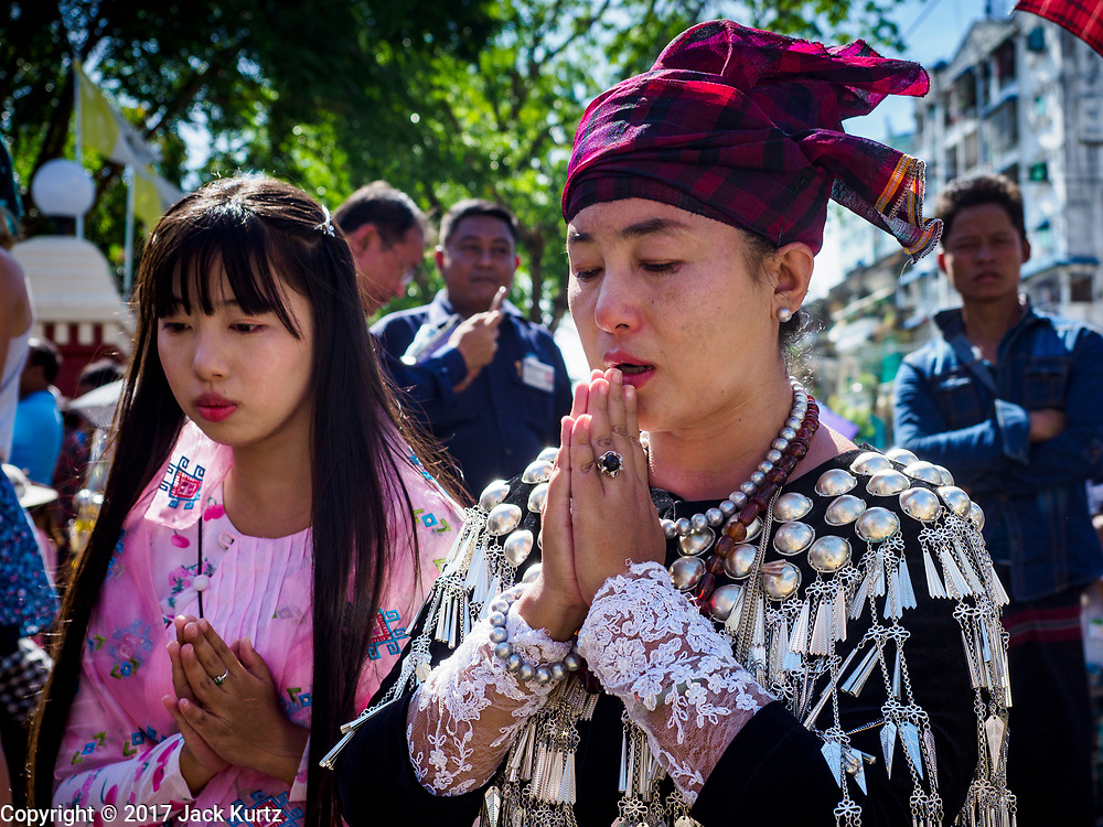 30 NOVEMBER 2017 - YANGON, MYANMAR: Women in traditional dress, who were not able to get into the cathedral, pray on the street during the Papal Mass at St. Mary's Cathedral in Yangon. Thursday's mass was his last public appearance in Myanmar. From Myanmar the Pope went on to neighboring Bangladesh.    PHOTO BY JACK KURTZ