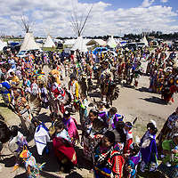 Native Americans participate in ceremonial Pow Wow at Browning, Montana with traditional clothing.