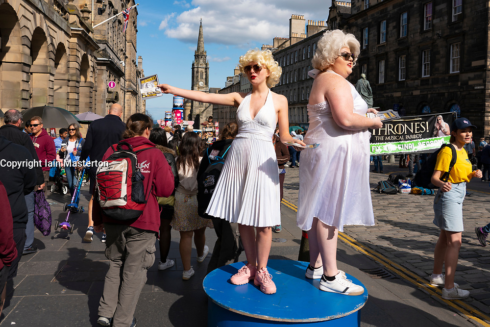 Edinburgh, Scotland, UK. 15 August 2019. Warm sunny weather in Edinburgh brought thousands of tourists onto the Royal Mile to enjoy the many street performers and actors promoting their shows during the Edinburgh Festival Fringe. Pictured cast of Heroin(e) for Breakfast.  Iain Masterton/Alamy Live News ++ Editorial Use Only ++