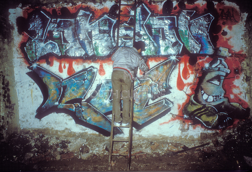 Man on ladder leaning on graffiti wall, U.S.A, 1980s.