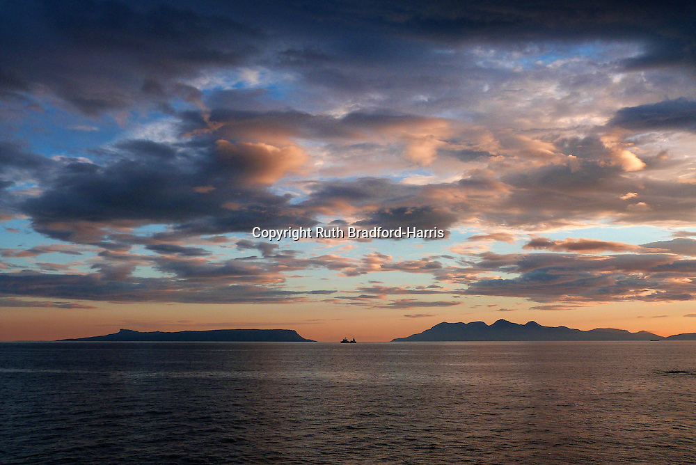A stunning view of the Small Isles of Eigg &amp; Rum in silhouette from the shore at Mallaig at sunset. A dramatic cloudscape and a perfectly placed ship silhouette complete the scene. Amazingly, this image was taken at approaching midnight on Midsummer's Day.<br /> <br /> Date taken 24 June 2016.