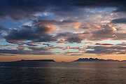 A stunning view of the Small Isles of Eigg &amp; Rum in silhouette from the shore at Mallaig at sunset. A dramatic cloudscape and a perfectly placed ship silhouette complete the scene. Amazingly, this image was taken at approaching midnight on Midsummer's Day.<br />