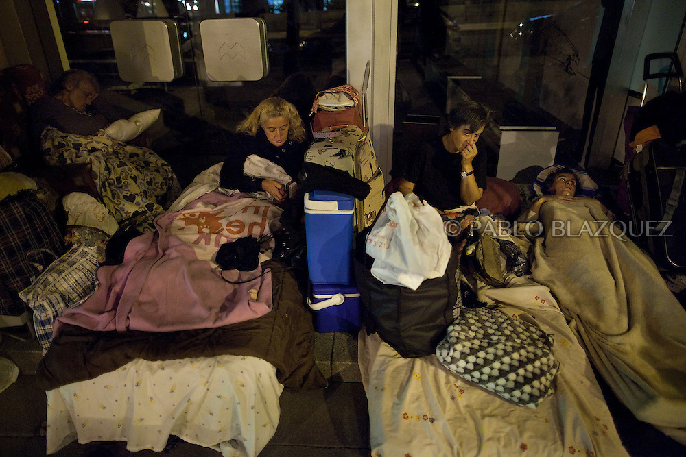 (L-R) Carmen Castilla 77, her daughters Rosa Maria Sastre Castilla 46, Carmen Aurora 49 and Antonia 45 get ready to sleep in the front door of a store on September 3, 2012, in Madrid, Spain. The family of four were evicted from the flat they were renting on April 24th, after Rosa lost her job and the main income of the family. They couldn't afford to pay anymore their rent. Social Services provided with temporally shelter for 15 days, but after that they found themselves living in the street. They have wrote to the Spanish Prime Minister, the King, the Prince and the Queen of Spain, the President of Madrid but all answers received were saying that they were really sorry about their situation but there was nothing they could do on their hands, referring them to the Social Services. They have registered their census in a piece of street of Madrid. Neighbors often give them a hand providing food, blankets, charging mobiles or making their laundry. The family lives of their mother's widow's pension, some money they get from visually impaired Antonia's welfare allowance, and whatever income the sister Carmen Aurora can get working as a concierge at a nearby building.They sleep rough in a store front door nearby. Carmen 77, with back and heart problems, sleeps sitting on her armchair as she is not able to stand up from ground level if she would sleep on top of a mattress.