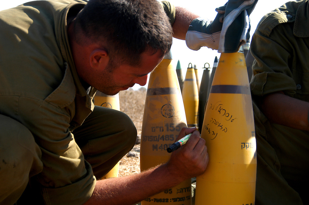 """IDF artillery soldier writing """"to Nasrallah with love"""" on an about to be fired canon shell. 2nd Lebanon War. Israel, August 2006."""