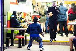 """© Licensed to London News Pictures . 24/12/2016 . Manchester , UK . A man dances inside Funky Chicken takeaway . Revellers out in Manchester City Centre overnight during 2016's second """" Mad Friday """" , named for historically being one of the busiest nights of the year for the emergency services in the UK . Photo credit : Joel Goodman/LNP"""