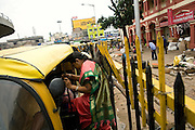 A woman is stepping into a rickshaw next to the Bangalore City Market, Karnataka, India. Near this very same place Shafiq Syed, now 34, used to sleep and make a meagre living when he escaped various times from his father's home at the tender age of 11 to live as a street child here first, and then in Mumbai. It was during the time living next to Churchgate train station, in central Mumbai, that he was selected to become the main character for the cast of Cannes' Camera D'Or 1988 winner Salaam Bombay. After the movie he failed to become a star, fell back into poverty and lived on the streets for years before he moved on to become a rickshaw (tuk-tuk) driver in his home city of Bangalore, Karnataka State, India.