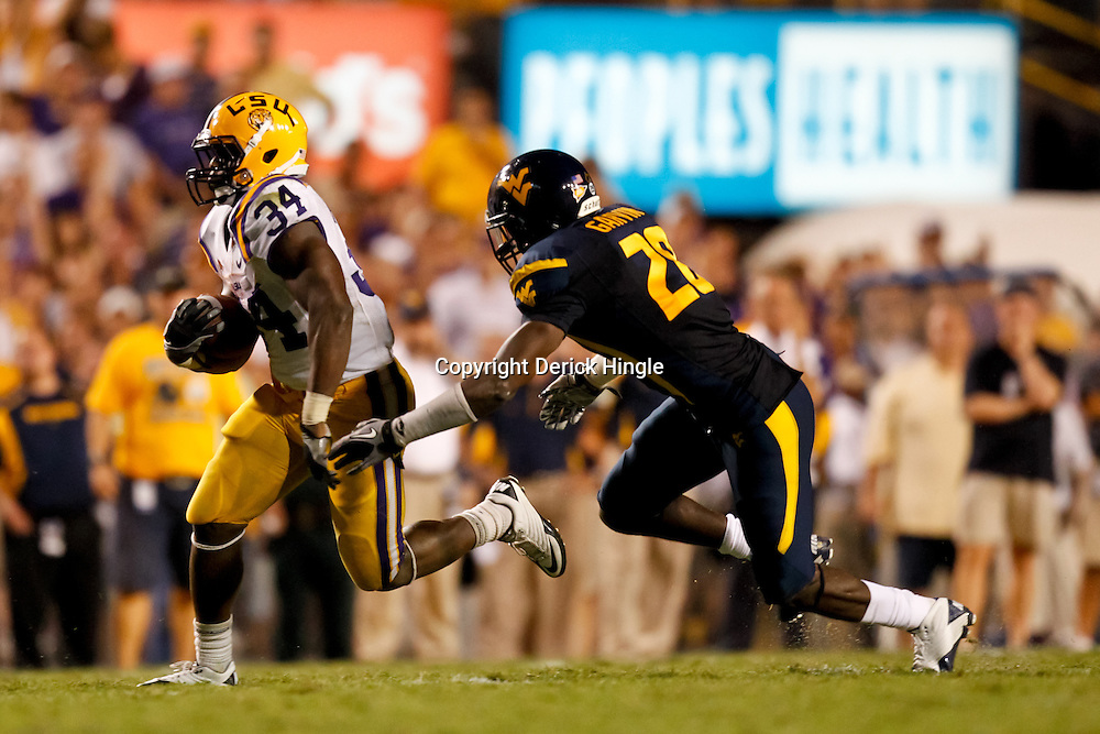 Sep 25, 2010; Baton Rouge, LA, USA; LSU Tigers running back Stevan Ridley (34) runs past West Virginia Mountaineers cornerback Darwin Cook (28) during the second half at Tiger Stadium. LSU defeated West Virginia 20-14.  Mandatory Credit: Derick E. Hingle