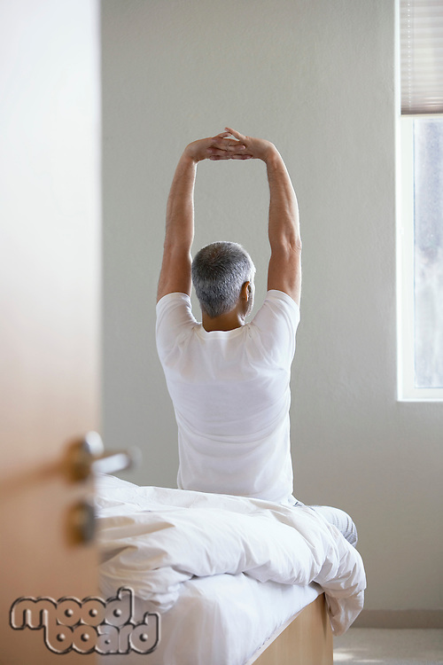 Man stretching sitting on edge of bed back view