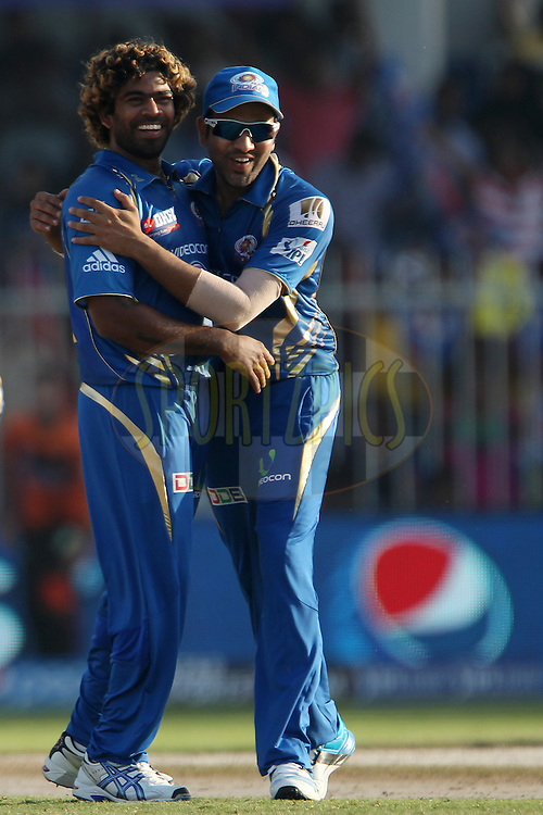 Lasith Malinga of the Mumbai Indians celebrates the wicket of Dinesh Karthik of the Delhi Daredevils with Rohit Sharma captain of of the Mumbai Indians  during match 16 of the Pepsi Indian Premier League 2014 between the Delhi Daredevils and the Mumbai Indians held at the Sharjah Cricket Stadium, Sharjah, United Arab Emirates on the 27th April 2014<br /> <br /> Photo by Ron Gaunt / IPL / SPORTZPICS