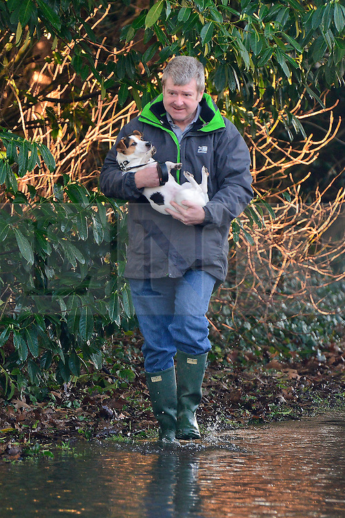 © Licensed to London News Pictures. 12/01/2014. Wraysbury, UK. A man carries a dog through floodwater. Flooding in Wraysbury, Berkshire today 12th January 2014.  Flooding and property damage is expected to continue along the River Thames.  Large areas of Britain are experiencing flooding after wet weather. Photo credit : Stephen Simpson/LNP