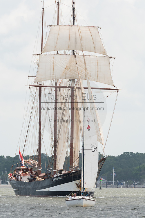 A tiny sailboat tries to sail out of the way of the Dutch three-masted schooner Oosterschelde during the parade of sails kicking off the Tall Ships Charleston festival May 18, 2017 in Charleston, South Carolina. The festival of tall sailing ships from around the world will spend three-days visiting historic Charleston.
