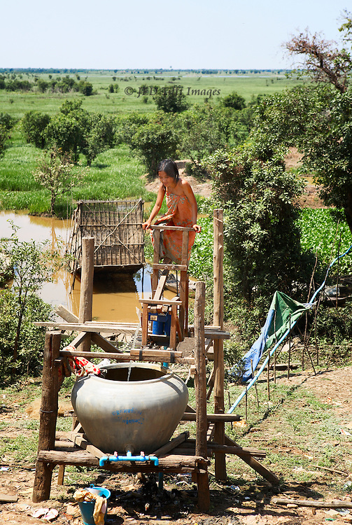In rural Cambodia, a teenaged girlusing a pedall-driven pump  irrigates a garden beyond from a huge vat of water.
