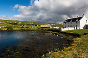 Vidlin port in the sun before a threatening cloud comes past overhead, Shetland.