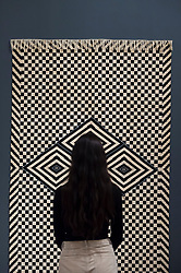 "© Licensed to London News Pictures. 09/10/2018. LONDON, UK. A visitor views ""Serape, Queretaro, Mexico"",  1850-1950.  Preview of the UK's first exhibition of works by German artist Anni Albers at Tate Modern who used the ancient art of hand-weaving to produce works of modern art.  Over 350 of her artworks from major collections from Europe and the US are on show 11 October to 27 January 2019.  Photo credit: Stephen Chung/LNP"