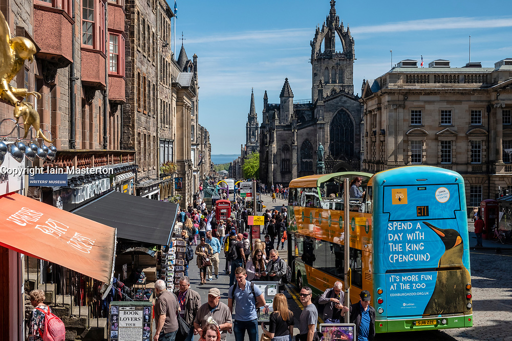 View along the Royal Mile with many tourists and tour bus in Old Town of Edinburgh, Scotland, UK