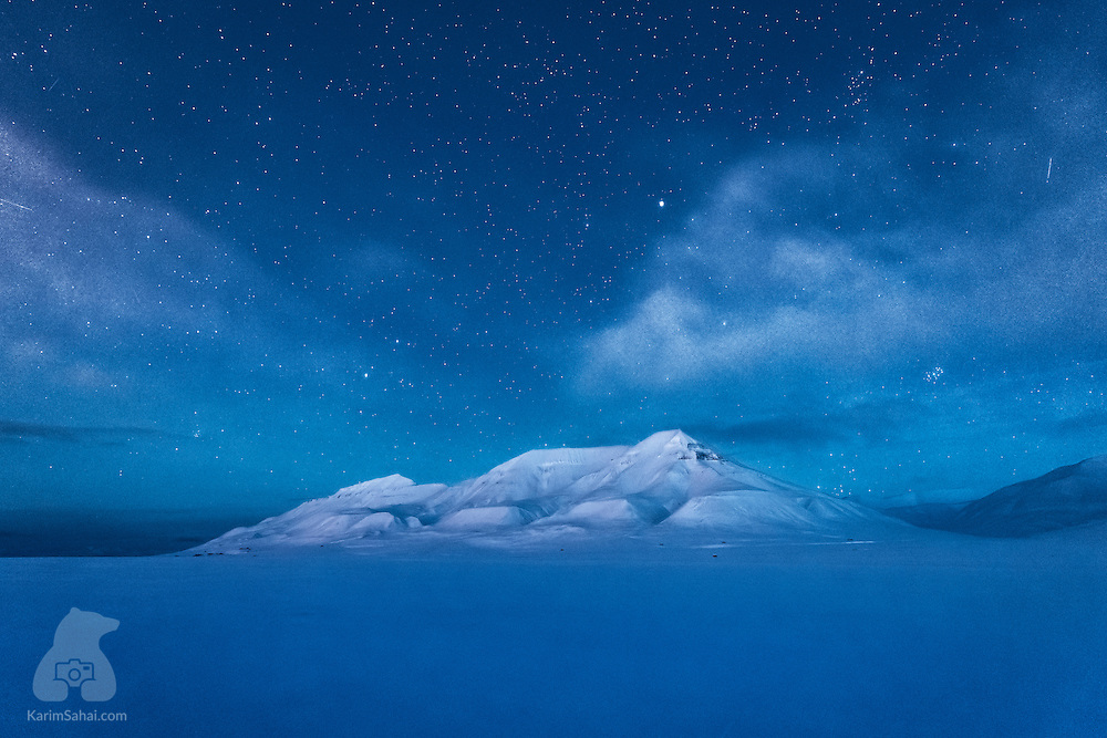 The Hjortfjellet mountain rises from the floor of the Advent valley, clouds glow and stars sparkle. This is the Polar Night. This is Svalbard.