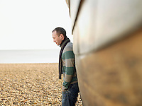 Man leaning against wooden hull of boat on beach side view