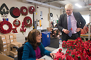 © Licensed to London News Pictures. 08/10/2014. Richmond, UK The Mayor of London, Boris Johnson, and Zac Goldsmith MP tour 'The Poppy Factory' in Richmond, Surrey, today 9th October 2014.  Melanie Waters, the Chief Executive, briefed the Mayor and Zac Goldsmith on The Poppy Factory's 'Getting You Back to Work' initiative. To date, The Poppy Factory has supported nearly 500 wounded, injured or sick ex-service men and women back into the workplace through this new, nationwide initiative, through connections with commercial organisations like Transport for London. The goal is to help over 1,000 veterans by 2018. Employees at The Poppy Factory have made some 13 million poppies, 950,000 thousand remembrance crosses and 96,000 wreaths for The Royal British Legion Remembrance events in November. The Annual Field of Remembrance at Westminster Abbey is also planned and delivered by The Poppy Factory. Photo credit : Stephen Simpson/LNP