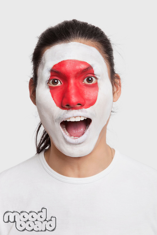 Portrait of surprised young mixed race man with Japanese flag painted on face against white background