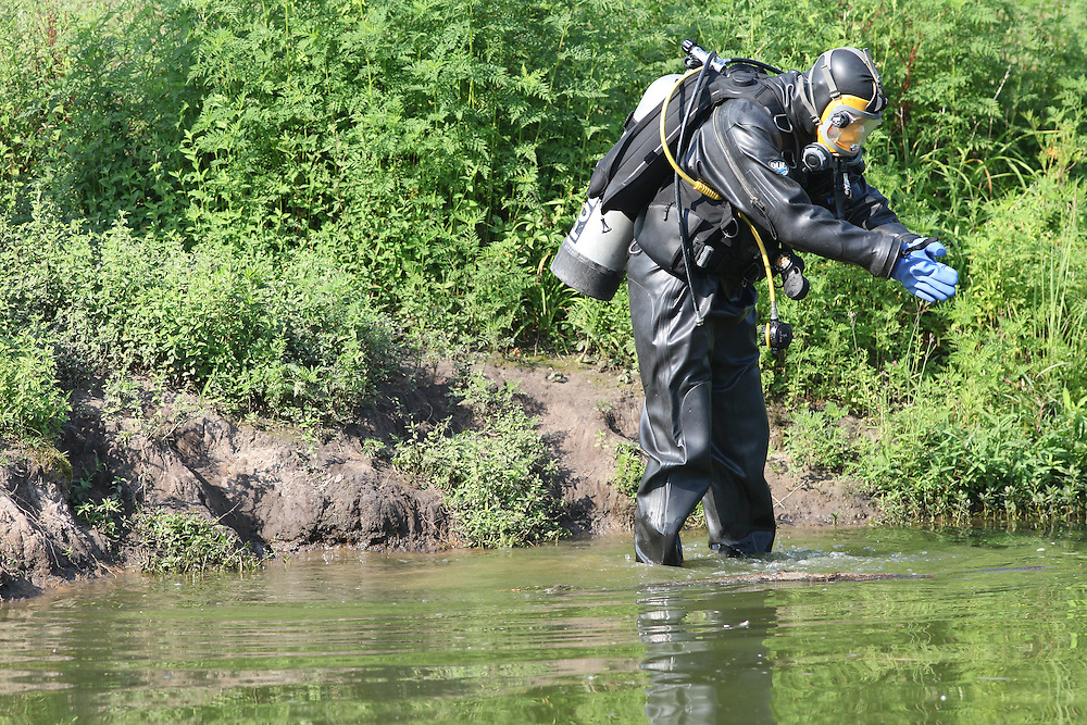 ANDREW KNAPP/STAFF -- July 3, 2012 -- A diver prepares Tuesday to search a pond off Mulberry Street in West Ashley's Ardmore community, where authorities again looked for evidence in the murder case of 17-year-old Marley Lion. Lion was fatally shot in a nearby parking lot.