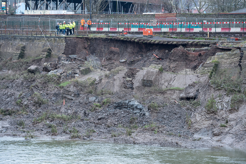 """© Licensed to London News Pictures. 24/01/2020. Bristol, UK. Engineers examine a stretch of collapsed wall and pathway by the river Avon on Cumberland Road in Spike Island, Bristol. The cycle path between the river and the road, known as the """"Chocolate Path"""" because the square cobbles look like chocolate blocks, has been closed for two years since December 2017 due to subsidence but no work had been done though funding had been established. It is reported that Cumberland Road, which is a major bus route, will remain closed for the foreseeable future which will cause further issues with Bristol's already congested traffic. Photo credit: Simon Chapman/LNP."""