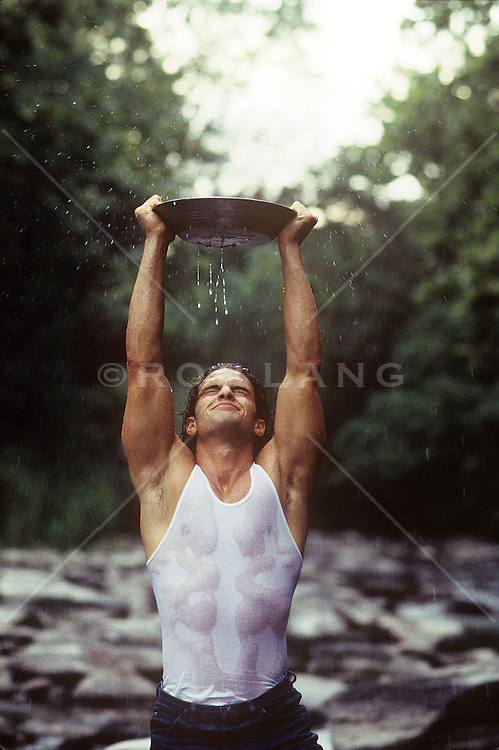 man with muscular arms and body holding a pan filled with water above his head in a stream