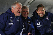 AFC Wimbledon temporary manager coach Glyn Hodges, AFC Wimbledon coach Vaughan Ryan and AFC Wimbledon goalkeeping coach Ashley Bayes smiling and laughing whilst sat in dugouyt during the Leasing.com EFL Trophy match between AFC Wimbledon and Leyton Orient at the Cherry Red Records Stadium, Kingston, England on 8 October 2019.