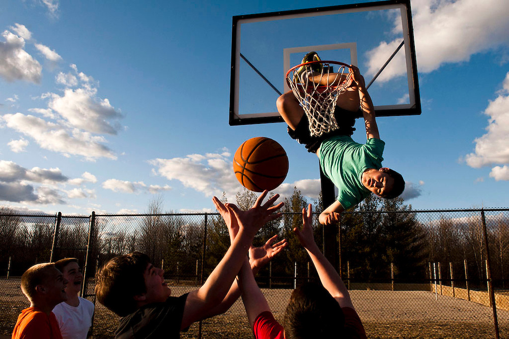 Lauren Justice | MLive.com<br /> <br /> Luke Zackrison, 15, hangs from the hoop surrounded by friends on the basketball courts at Creasey Bicentennial Park Fri., March 29.