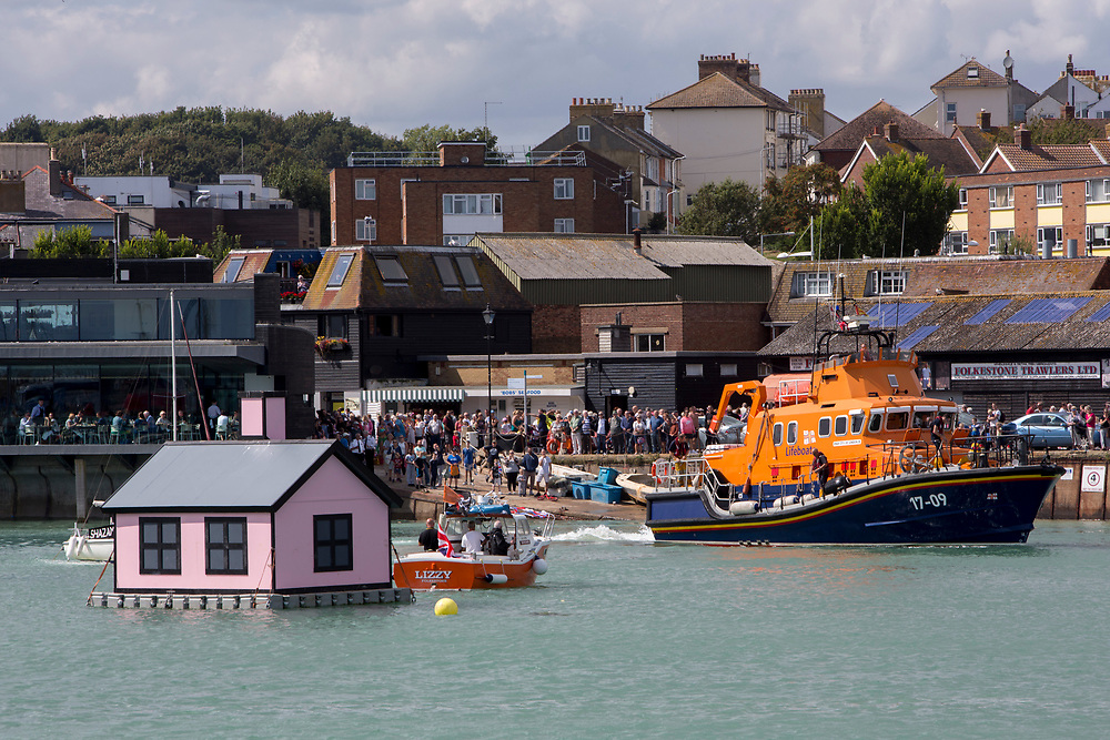 The Royal National Lifeboat Institution RNLI Dover Life boat (17-09) parked up next to a floating pink bungalow in Folkestone harbour built by the artist Richard Woods as part of the 2017 Folkestone Triennial  Folkestone, Kent. UK.. (photo by Andrew Aitchison / In pictures via Getty Images)