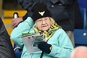 An elderly lady Oxford United fan reads her match day programme during the EFL Sky Bet League 1 match between Oxford United and AFC Wimbledon at the Kassam Stadium, Oxford, England on 13 April 2019.
