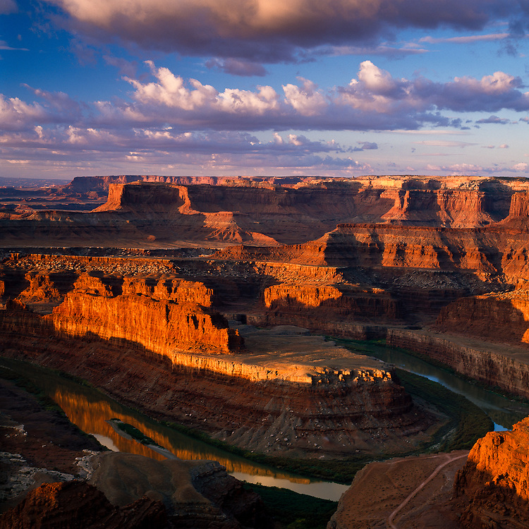 Early morning light shines on the rock formations of Dead Horse Point State Park, and is reflected on the twists and turns of the  river.